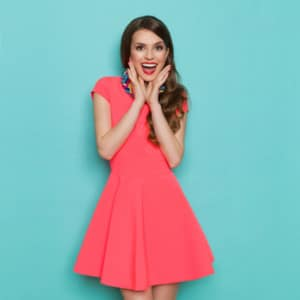 Shouting beautiful young woman in pink mini dress posing with hands on chin. Three quarter length studio shot on turquoise background.